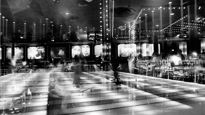 Time exposure of dance floor, table area and pictures on wall at Club 2001.
