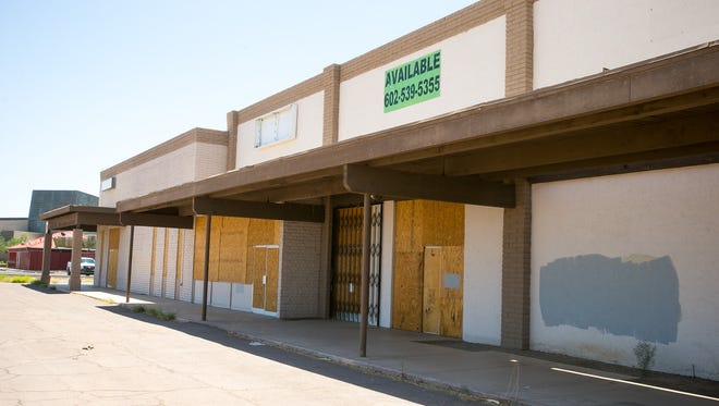 The boarded-up storefront of an old Smitty's grocery store in downtown Peoria.