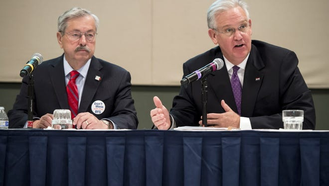 Missouri Gov. Jay Nixon, right, signed legislation on Thursday that will limit the amount of money municipalities in the state can generate from court fees and tickets.
