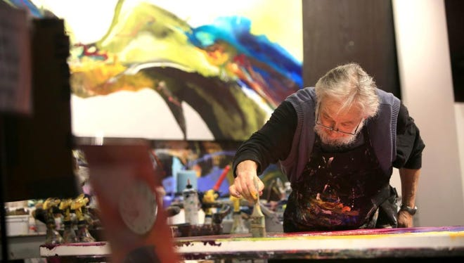In this November 2015 photo, artist Jonas Gerard takes part in a live painting performance at his studio on Lyman Street during the River Arts District Fall Studio Stroll.