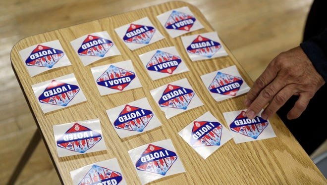 In this Oct. 22, 2016, file photo, a volunteer hands out stickers during early voting in Las Vegas.