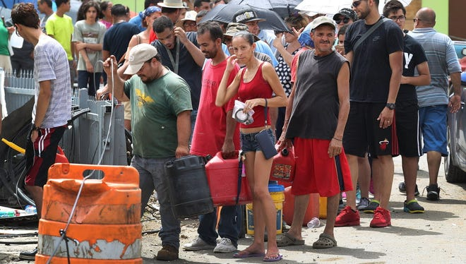 People wait in line for gas Sept. 27, 2017, as they deal with the aftermath of Hurricane Maria in Corozal, Puerto Rico.