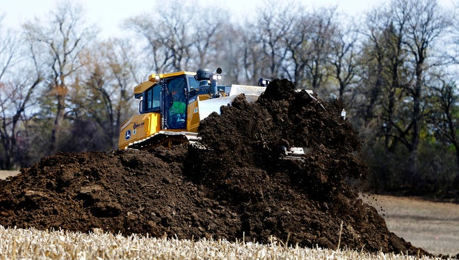 A bulldozer pushes dirt Monday at the Foxconn site in Racine County as earth-moving work began in preparation for construction of the electronics factory.