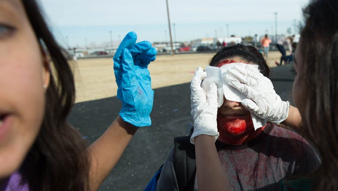 Ciliana Salaiz, center, gets treated for fake head and facial wounds after a simulated bombing at Las Cruces High School, which was part of a real world learning experience for the school's Health and Human Services Academy students Friday, Feb. 2, 2018.