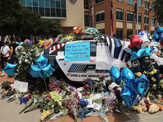 People visit a growing memorial at the Dallas police department's headquarters in downtown Dallas following the deaths of five police officers on Thursday,  July 9, 2016.
