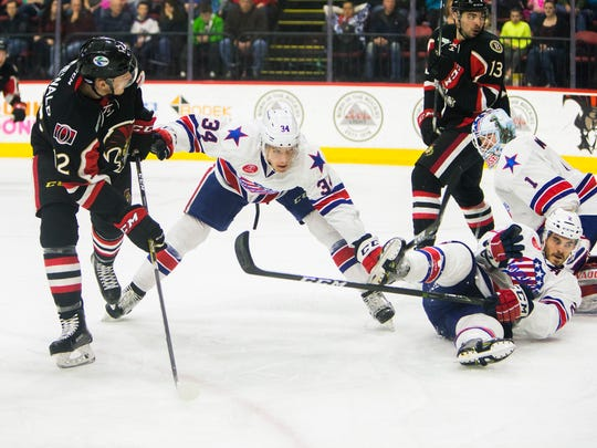 Rochester Americans defenseman Casey Nelson, center, blocks a shot attempt by Binghamton Senators right wing John Rodewald during the second period Saturday in Binghamton.