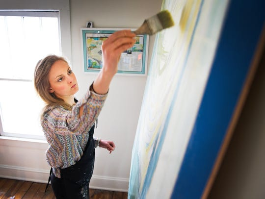 Kiah Ann Bellows paints in her studio space at Art