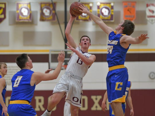 Evan Gitter (13) of Omro tries to take a shot as Nicholas Narges (24) of Campbellsport goes for the block. The Omro Foxes hosted the Campbellsport Cougars Tuesday evening, November 21, 2017 at the Den.