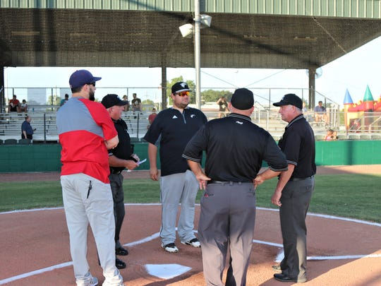 Coaches exchange lineups during a game between the Cane Cutters and Twins on May 31. The  Cutters defeated the Twins, 8-0, on Thursday night.