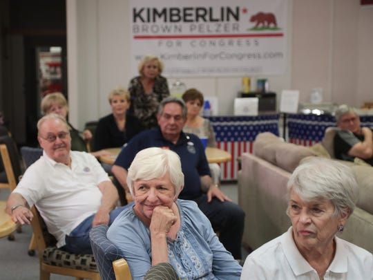 Supporters of Kimberlin Brown Pelzer listen to initial election results in La Quinta, Calif., Tuesday, June 5, 2018.