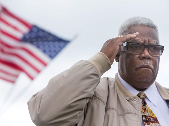 Marine veteran Lynwood White of Wilmington salutes during the playing of taps.