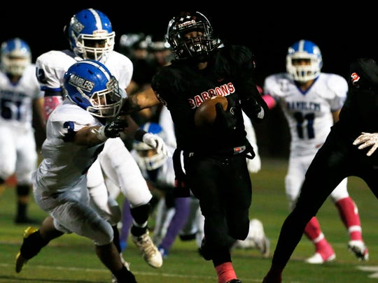 The Ramblers of Carteret High School traveled down the New Jersey Turnpike to take on the Barrons of  Woodbridge High School for a varsity football game in Woodbridge on Friday October 14, 2016.Woodbridge's # 5 (Cneter) Da'Avian Ellington breaks free from Carteret tackler's for a 1st half touchdown.