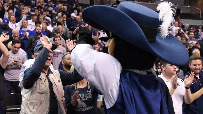The Xavier Musketeers mascot high-fives actor Bill Murray after the semifinals of the West Regional of the 2017 NCAA Tournament, where Xavier upset the Arizona Wildcats at SAP Center.