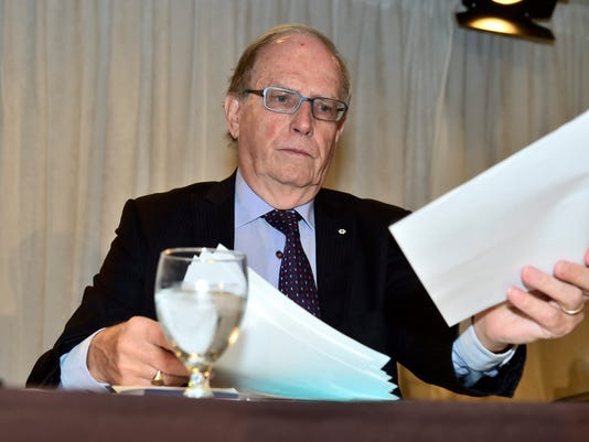 Canadian law professor Richard McLaren arranges papers after speaking at a news conference to present his findings into allegations of a state-backed doping conspiracy involving the 2014 Winter Olympics in Sochi, Russia, in Toronto, Monday, July 18, 2016. (Frank Gunn/The Canadian Press via AP)