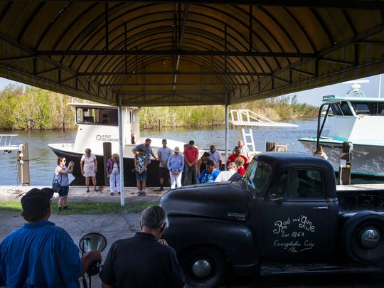 People bow their heads as Pastor Bob Wallace leads them in prayer before the Blessing of the Stone Crab Fleet at the Rod & Gun Club in Everglades City on Saturday, Sept. 30, 2017.