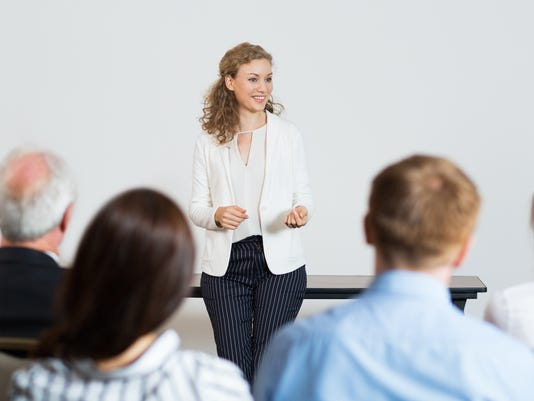Successful Young Businesswoman Speaking in front of Audience at