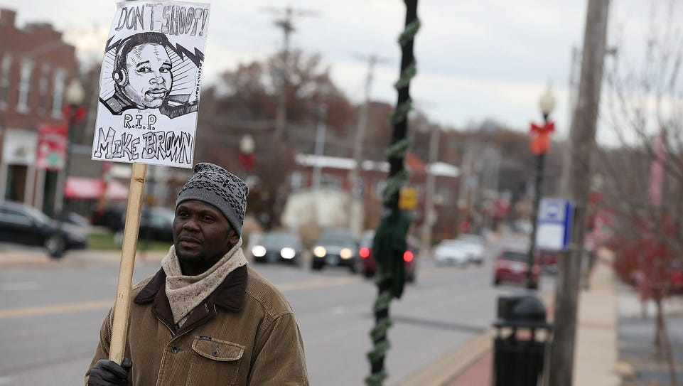 A demonstrator holds a sign with an image of Michael