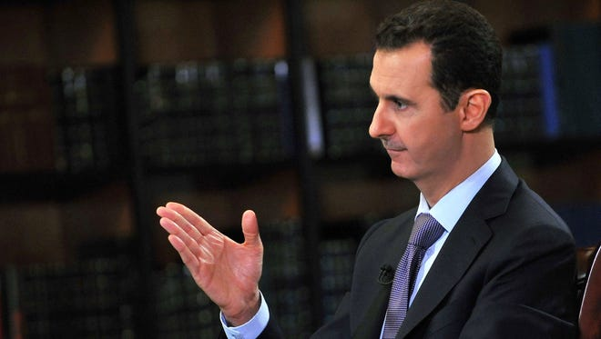 Syrian President Bashar Assad gestures as he speaks during an interview with Italy's RAI News 24 TV on Sunday.