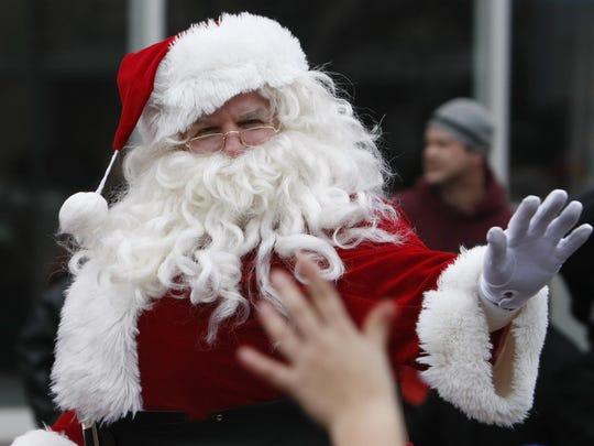 Santa Claus waves during Springfield's downtown Christmas parade.