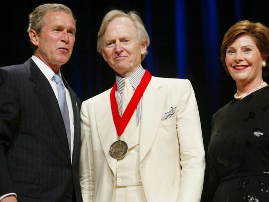 FILE - In this April 22, 2002 file photo, President Bush, left, poses with author Tom Wolfe, center, and first lady Laura Bush during the National Endowment for the Arts National Medal Awards ceremony at Constitution Hall in Washington . Wolfe was a recipient of the National Humanities Medal. Wolfe died at a New York City hospital. He was 87. Additional details were not immediately available. (AP Photo/Pablo Martinez Monsivais, File)