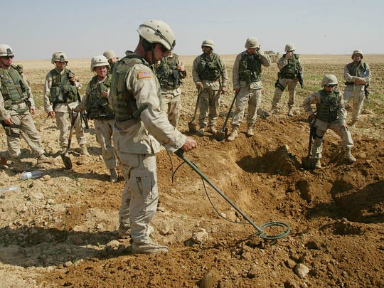 This Oct. 9, 2003, photo shows soldiers from the U.S. Army's 720th Military Police Battalion watching as a mine sweeper look for weapons in a hole they dug during a raid on a farmland outside Tikrit, Iraq. The Obama administration announced Friday that the U.S. will no longer produce or acquire anti-personnel land mines and plans to join an international treaty banning their use.