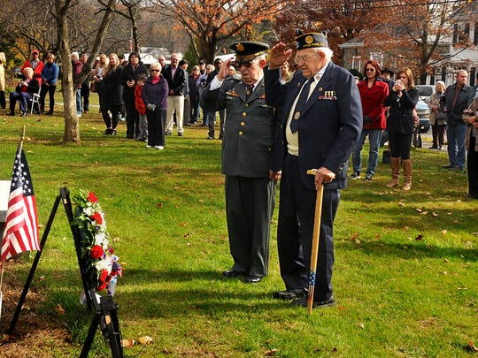 After laying a wreath at the Hyde Park War Memorial, General Eliot Hermon, left foreground, of Wallkill, and Ralph Ousterhoudt, who fought in the Battle of the Bulge during World War II, salute during the Hyde Park Veterans Day ceremony Tuesday behind Town Hall.