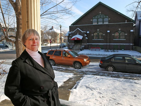 Sally Spiers, president of the Chatham Arch Neighborhood Association, stands on her porch across from the Phoenix Theatre on Park Avenue. The theater cited limited parking as a primary reason last week for moving from the site.