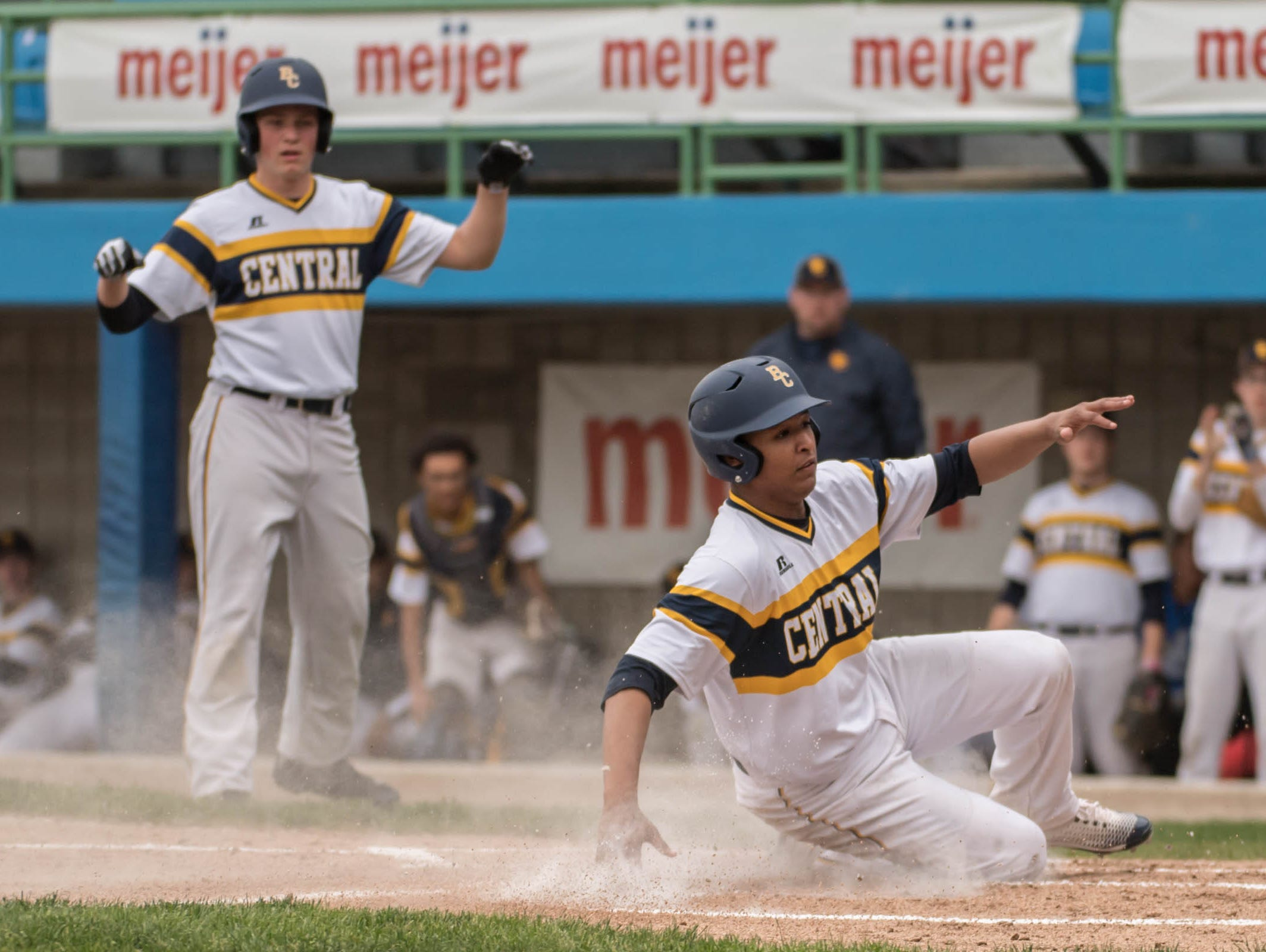 Battle Creek Central's Jordan Lawson slides home as Riley Cramer cheers him on during the Annual Play 4 May tribute game in honor Tim May at C.O. Brown Stadium on Monday.