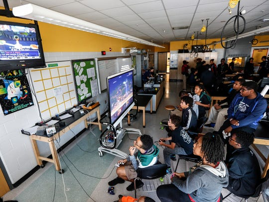 Students gather in front of a big screen to play Super
