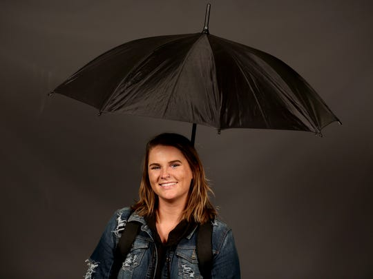 Statesman Journal entertainment reporter Abby Luschei tries the Baby Blooms Hands Free Sling Umbrella at the Statesman Journal in Salem on Thursday, Nov. 2, 2017.