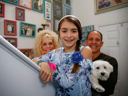 Summer Sesty, 11, is shown with her parents Victoria