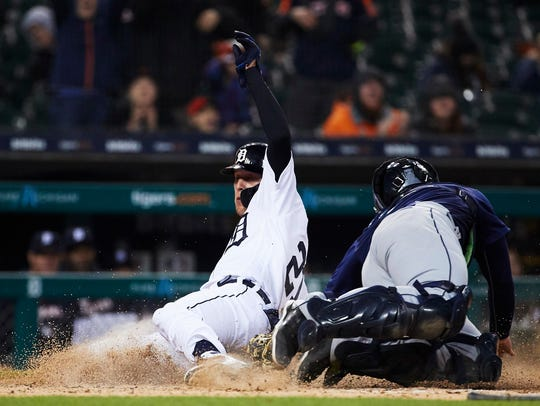 JaCoby Jones slides safely at home avoiding the tag by Seattle Mariners catcher David Freitas in the fifth inning Saturday.