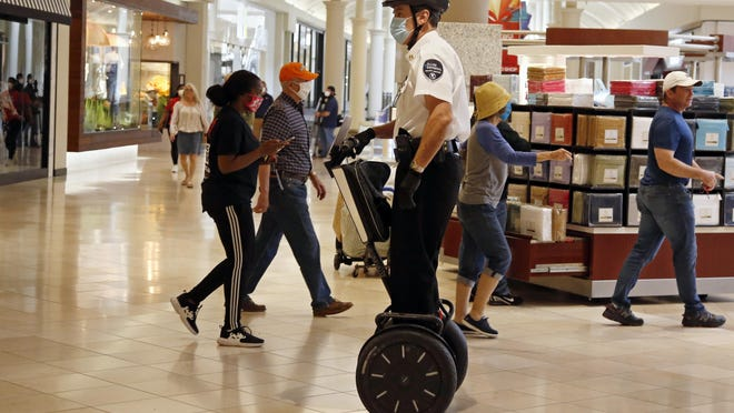 A security guard wearing a mask and riding a Segway patrols inside Penn Square Mall as the mall reopens Friday, May 1, 2020, in Oklahoma City.