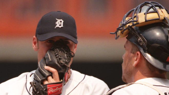 Detroit Tigers reliever Matt Anderson peeks from the sides of his glove as he talks to his catcher Joe Oliver after loading the bases in  a game against the Kansas City Royals on July 14, 2004.