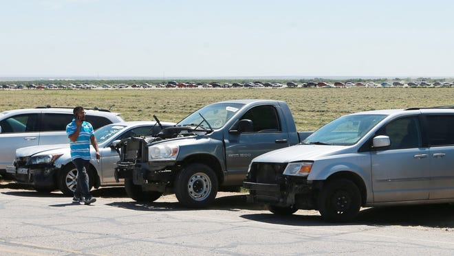 A man walks past cars that have been parked in a long line on the U.S. side of the Tornillo-Guadalupe Port of Entry. The head of the line is in the background. The vehicles are headed into Mexico.
