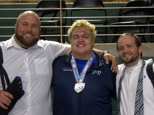 Wakulla senior wrestler Jacob Marin celebrates with assistant coach James Vernon, left, and head coach Will Pafford after Marin won a Class 1A state title at heavyweight on Saturday night in Kissimmee to become the sixth War Eagles champion all-time.