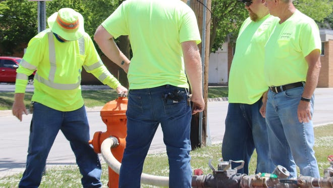 These city employees are not standing around the water cooler, they are actually working at preparing the splash pad on West Washington Street to be opened. City Administrator Bob Karls said the work is needed just in case the splash pad can open soon. However, the city is waiting on guidance from the state to learn when it can open.