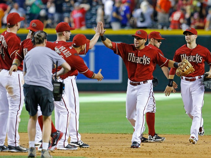 Arizona Diamondbacks left fielder David Peralta (6) (center) is greeted by Martin Prado following their 6-5 win over the Atlanta Braves in  their MLB game Sunday,  June, 8, 2014 in Phoenix.  Peralta hit his first career home run in the game.