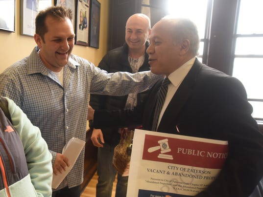 Here is Charles Florio of North Bergen, with JCM Investors of Paterson and Gary Tsirelman of New York, with Capitol 7 LLC. and Paterson Mayor Joey Torres at the conclusion of the auction. Florio won the bids on 62 of the 71 properties that were auctioned.