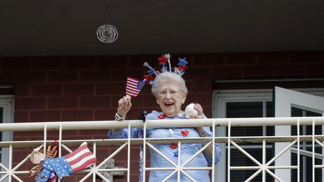 A resident of the Lambeth House, where a cluster of the coronavirus has formed, reacts from her balcony as opera singers Irini Hymel and Bryan Hymel sing to the quarantined residents in New Orleans on Friday.