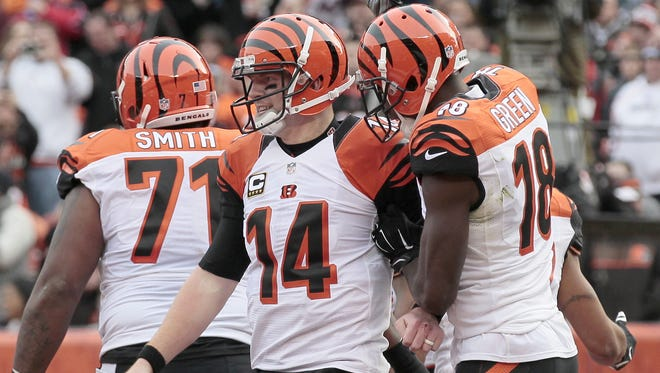 Cincinnati Bengals quarterback Andy Dalton (14) and wide receiver A.J. Green (18) celebrate after Dalton's rushing touchdown in the first quarter of the NFL Week 13 game between the Cleveland Browns and the Cincinnati Bengals at FirstEnergy Stadium in downtown Cleveland on Sunday, Dec. 6, 2015. At the half, the Bengals led 20-3.