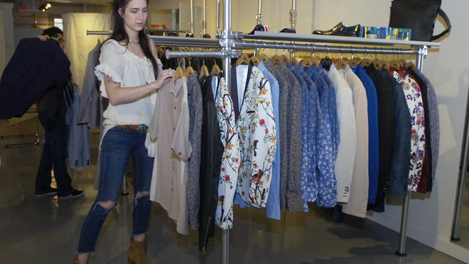 Kat Hilton, a sales person at Dolce Moda, replenishes a clothing rack.