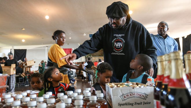 Rev. Charles Williams tells Detroit residents (right to left) Cordell McClain T'Yonna Wilson, Javin Land and Jeremiah Land to grab an apple juice as they gather food items with LaTonya Land in the King Solomon Baptist Church in Detroit on Wednesday October 7, 2015 during a weekly program supplying food for the needy in the city which has the highest rate of poverty in the U.S., according to new Census figures.