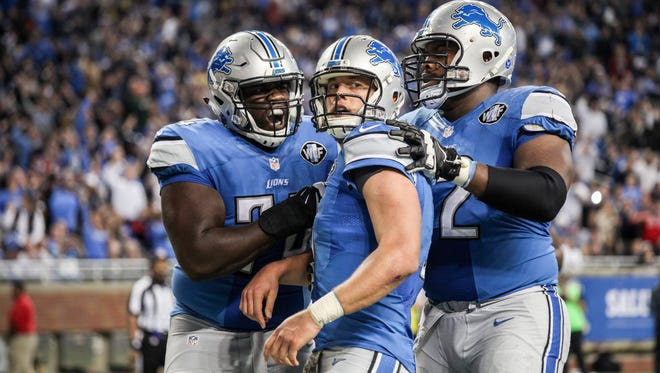 Detroit Lions Qb Matthew Stafford celebrates with his offensive line Larry Warford and Laken Tomlinson after running the ball in for a touchdown against Oakland Raiders, during the NFL game at Ford Field in Detroit on Sunday, Nov. 22, 2015.