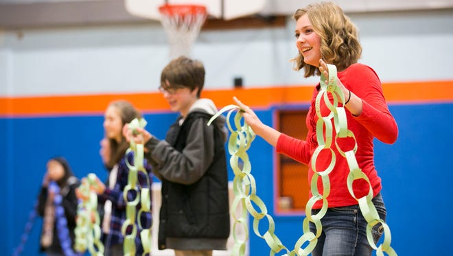 Whiteaker Middle School students hold up a chainlink with over 1,000 links from other schools in the area, with each link bearing another student's name. During next week's Great Kindness Challenge, students at Whiteaker are asked to sign their name on a slip of paper and add it to the chainlink, as a symbol of their commitment to ending bullying and promoting kindness.