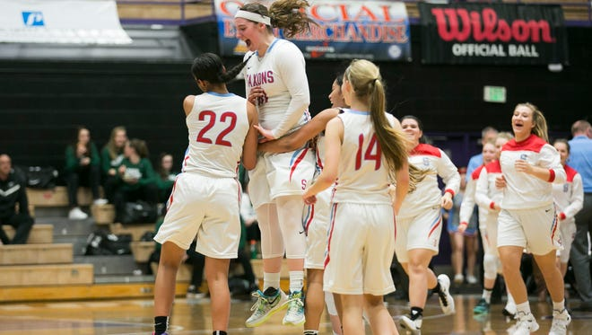 South Salem's Jordon Woodvine (10) jumps up to celebrate with teammate Evina Westbrook (22) after Westbrook made a half court basket in a game against Oregon City in the first round of the OSAA Class 6A state tournament on Wednesday, March 9, 2016, at the University of Portland. South Salem defeated Oregon City 46-30.