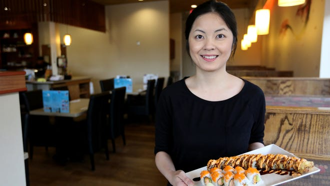 Di Ou, the manager at Momiji in Salem, holds a plate with a Spicy Salmon Tempura Roll and a Salem Roll.