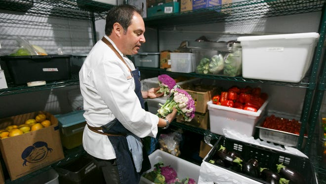 Chef Chris Turke looks at some of the fresh cauliflower at Farm to Fit's Portland kitchen on Saturday, Sept. 17. The gourmet meal-delivery service creates locally sourced, pre-made meals that they deliver to the Portland and now Salem area.