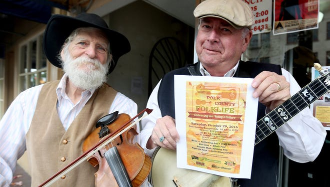 Truman Price, left, and John Adams invite people to join them for the Polk County Folk Festival at the Polk County Fairgrounds on Saturday.
