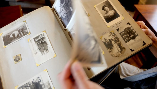 Val Springer looks through photo albums, dating from 1897 to 1988, she found in the garage of one of her rental homes. She hopes to track down descendants of the people in the photos.